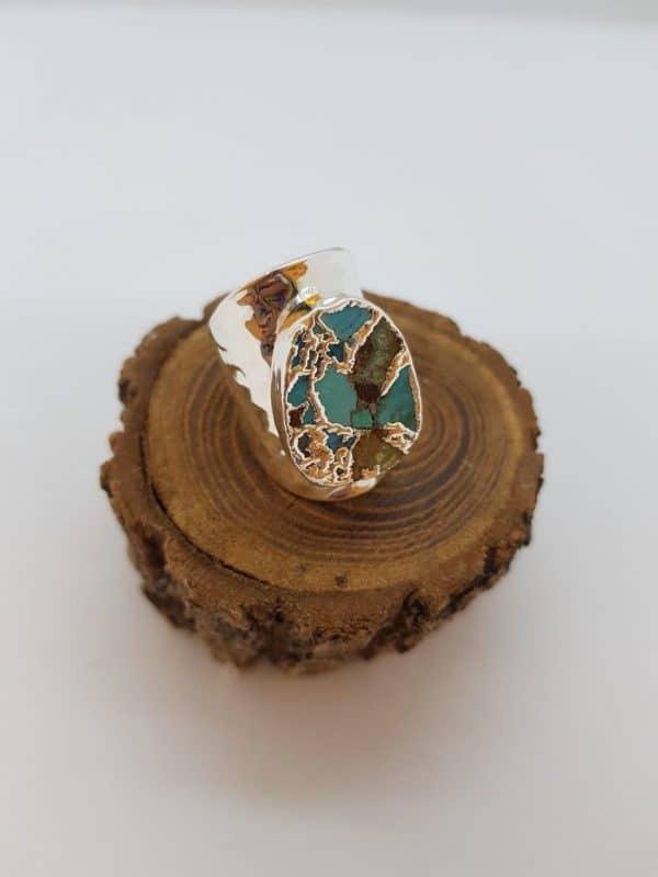 Bague de la marque Hypnochic, en métal argenté, couleur à dominante turquoise, pour un look chic et dans l'air du temps! Ajustable.
